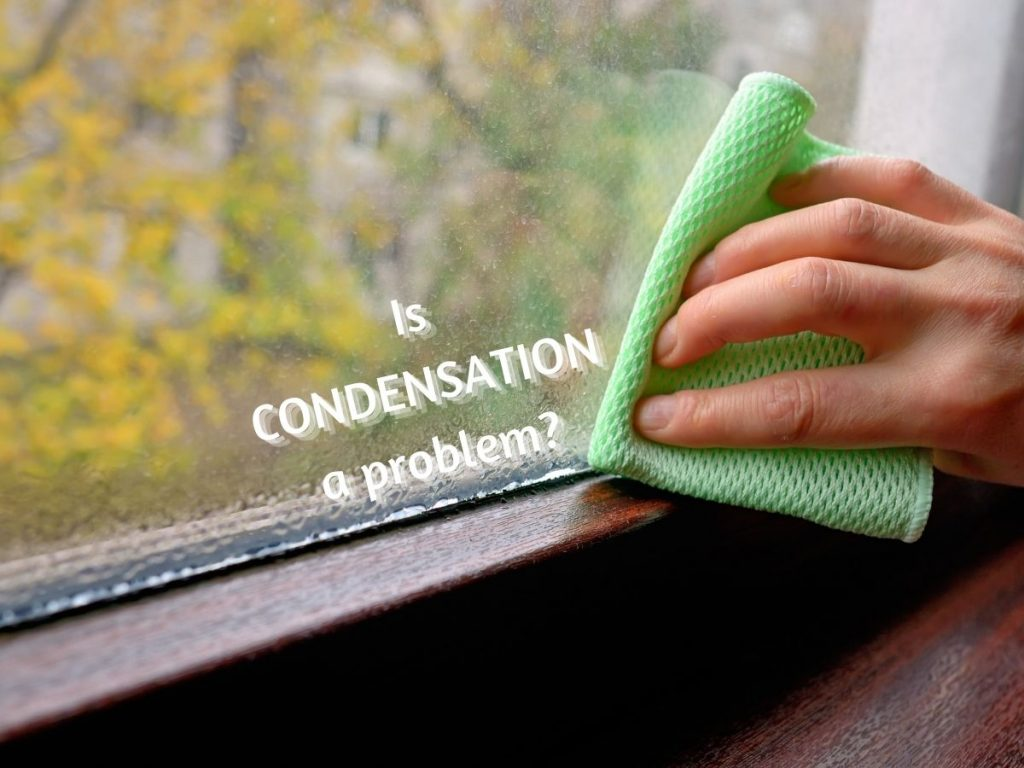 """Photo of a hand holding a cleaning cloth wiping condensation off a window with the caption """"Is Condensation a problem?"""""""