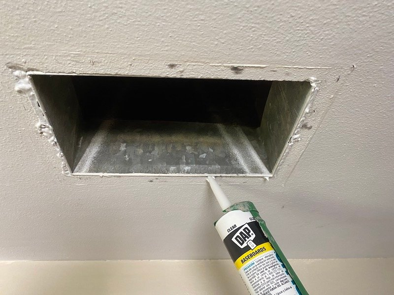A picture of an air duct with the cover off, and caulking around the outside of it. This helps prevent hot attic air from getting into the room.
