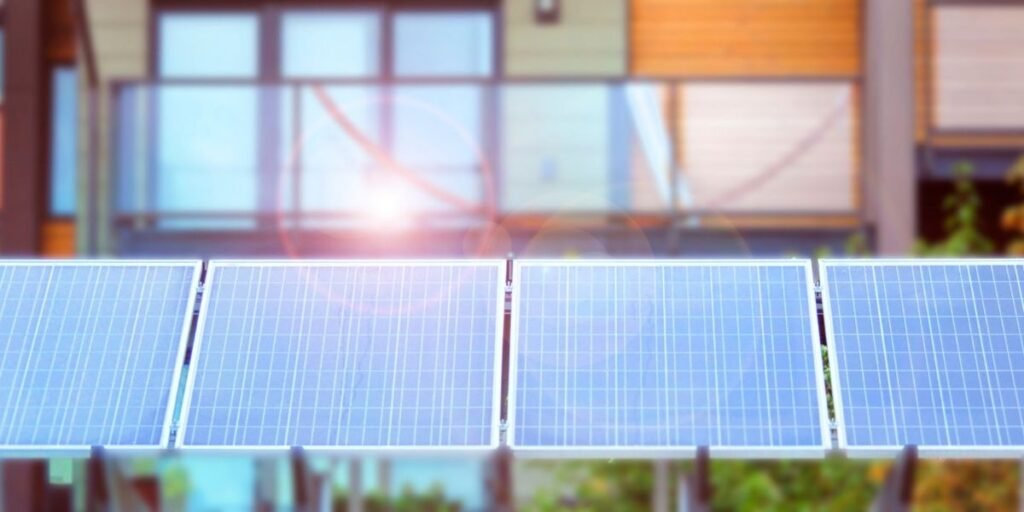 A picture of solar panels lined up with a modern house blurred out in the background, indicating net-zero energy buildings.