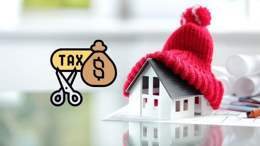 A picture of a little house wrapped in a warm hat made of yarn, with a tax money symbol being cut up to the left of it.