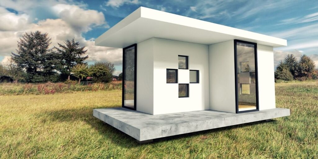 a small modern square looking house int he middle of a field.